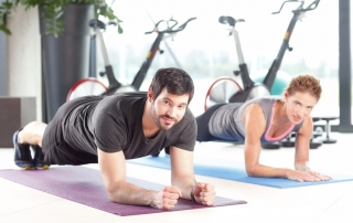Portrait of a man and woman training together at the gym. Personal trainers doing push ups at the fitness club.