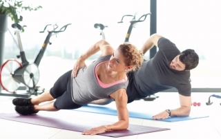 Portrait of a man and woman doing plank exercises at the gym.