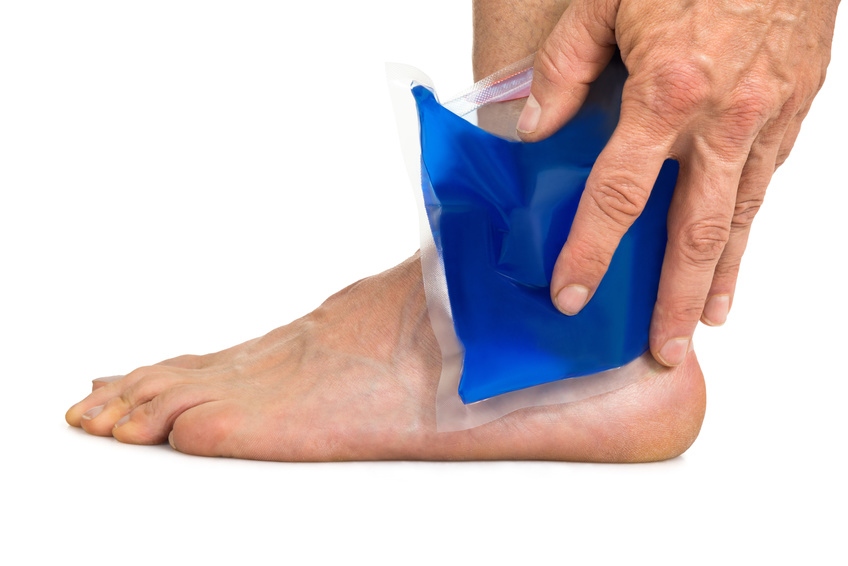 Close-up Of Hand Holding Cool Gel Pack On Ankle Over White Background