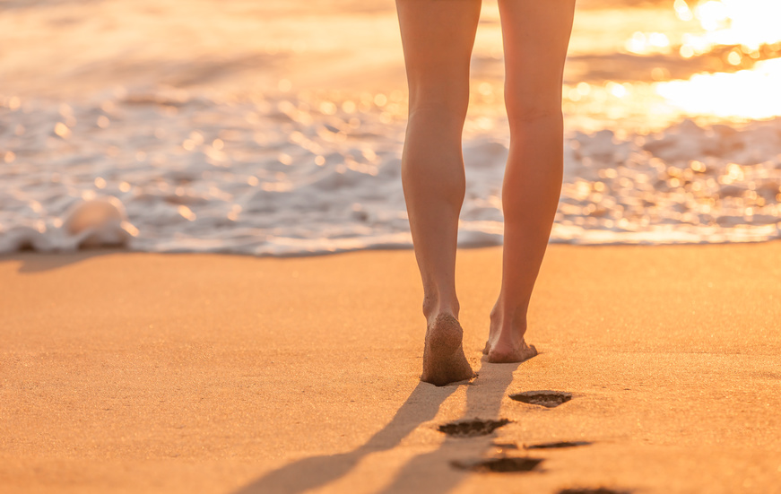 Woman walking on the beach during sunset.